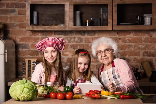 Enkelin und großmutter mit der tablette, die rezept sucht