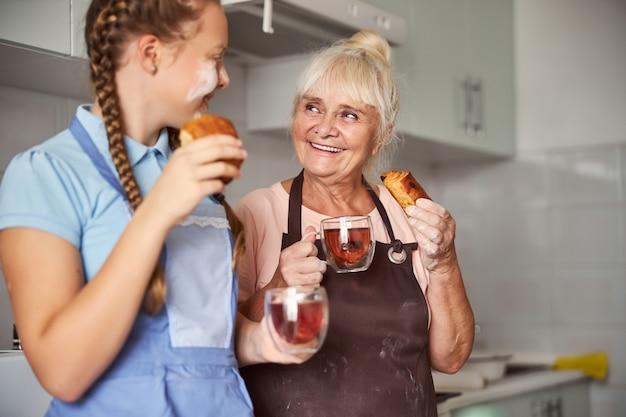 Enkelin und oma genießen sich beim tee