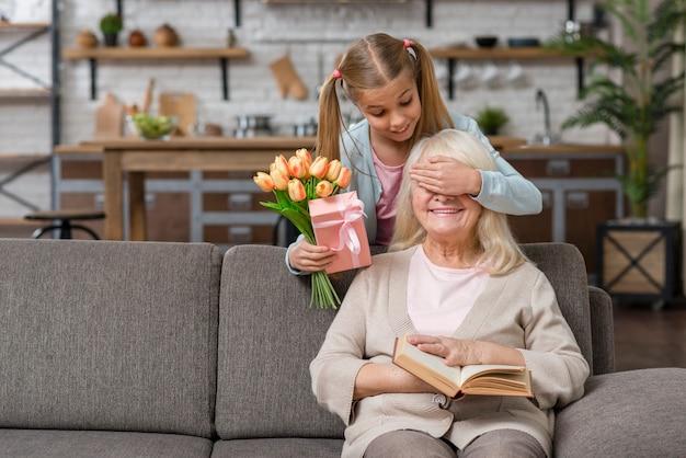 Enkelin, welche die augen ihrer großmutter bedeckt