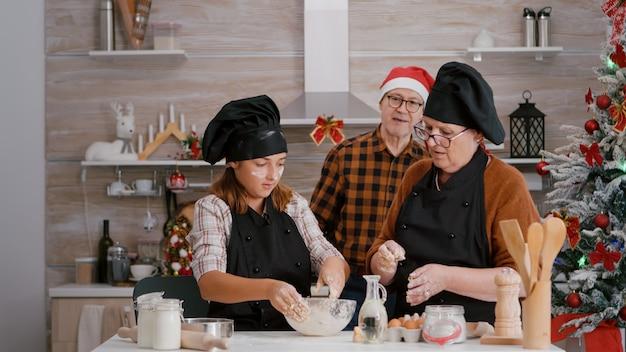 Enkelkind bereitet hausgemachten keksteig zu, während großmutterkaffee traditionelle feiertage zubereitet...