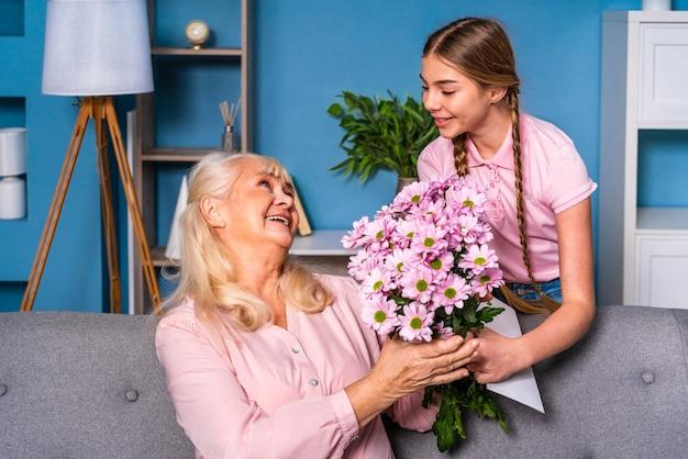 Enkelkind, das oma zu hause blumen präsentiert, glückliche häusliche lebensmomente