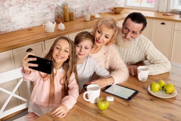 Enkelkinder des hohen winkels, die ein selfie mit ihren großeltern nehmen