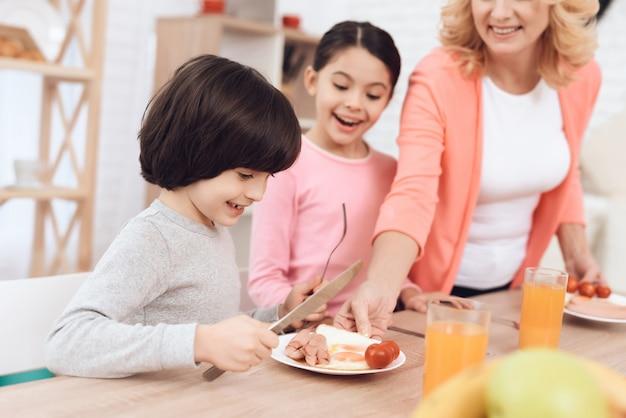 Enkelkinder, die das frühstück sitzt auf tabelle warten