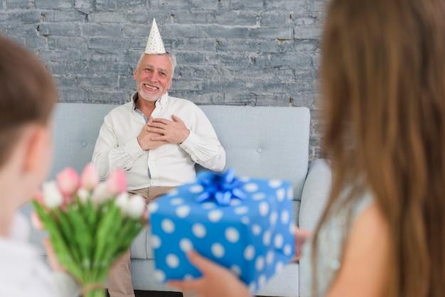 Enkelkinder, die ihrem überraschten großvater geschenke zeigen
