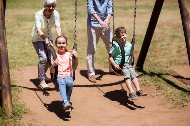 Enkelkinder haben spaß mit ihren großeltern im park