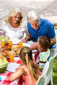 Enkelkinder mit den großeltern, die am rasen zu mittag essen