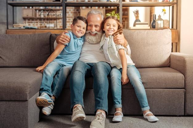 Enorme liebe. liebevoller älterer mann, der auf der couch sitzt und seine geliebten enkelkinder fest umarmt, während alle breit lächeln und glücklich sind, zusammen zu sein