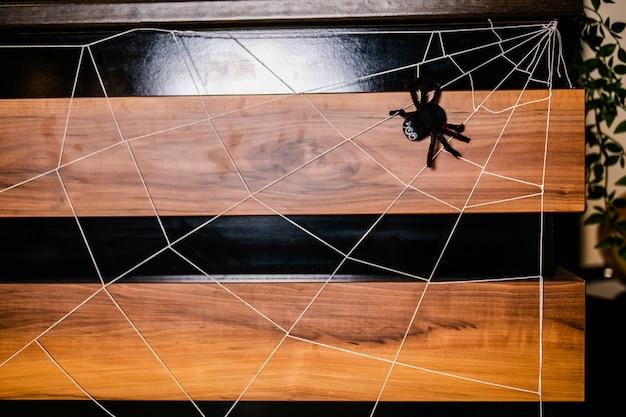 Enorme schwarze spinne mit netz auf der hölzernen wand auf der feier von halloween