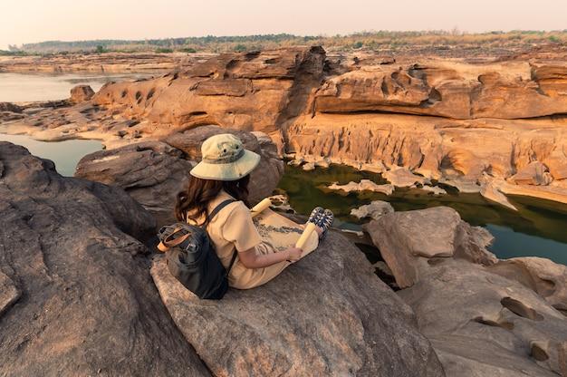 Entdecke asiatische frau, die auf felsenklippe mit blick auf papierkarte in sam phan bok grand canyon von thailand sitzt