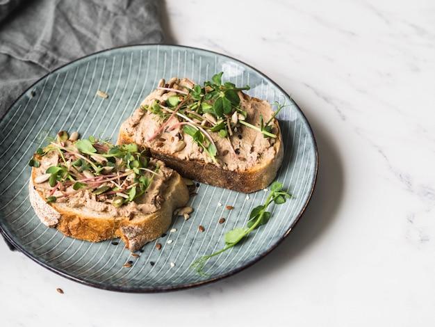 Ente mit zwei toasts mit pflaumenrillettenpastete mit sprösslingen und verschiedenen samen
