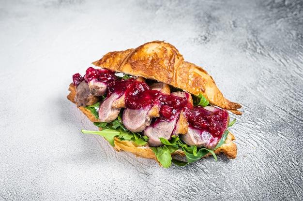 Entenbrust-croissant-sandwich mit steakscheiben, rucola und sauce. weißer tisch. draufsicht.