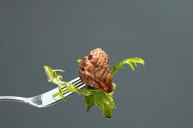 Entenfleisch und salat auf einer gabel isoliert auf schwarz