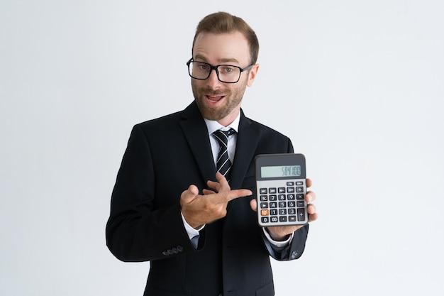 Enterprising bärtiger geschäftsmann, der auf taschenrechner zeigt