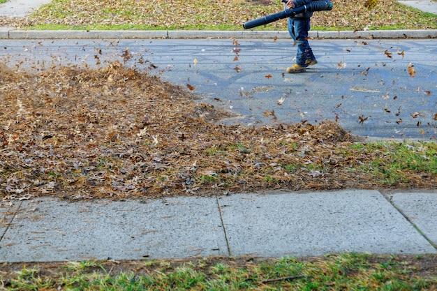 Entfernen von abgefallenen blättern im herbst blätter, die beim entfernen von abgefallenen blättern des herbstes aufgewirbelt werden