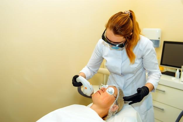 Entfernung von laserfalten. attraktiver arzt-kosmetiker, der die gesichtshaut in der schönheitsklinik verjüngt. junge frau, die schutzbrille während des verfahrens in der kosmetikklinik trägt