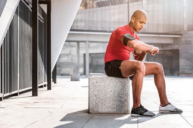Entfernungsprüfung. netter junger mann, der sein fitnessarmband betrachtet, während er die entfernung prüft