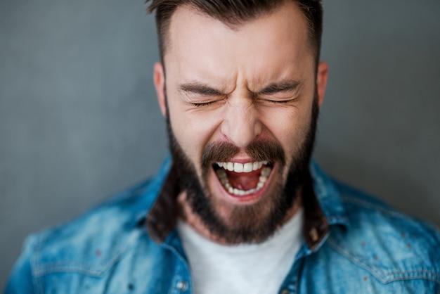 Entfesselte emotionen. frustrierter junger mann, der die augen geschlossen und den mund geöffnet hält, während er vor grauem hintergrund steht