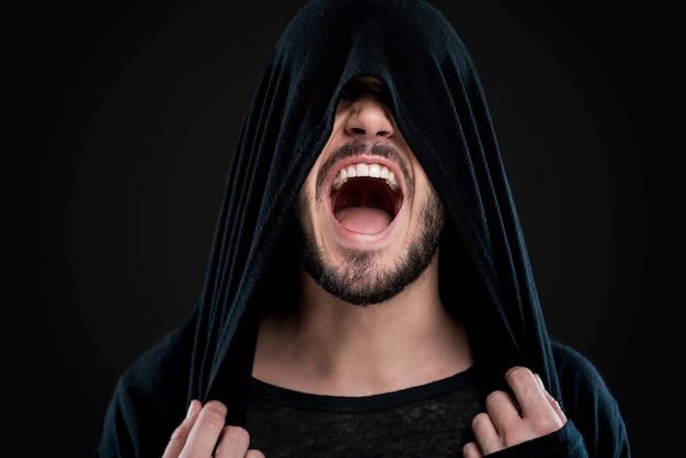 Entfesselte emotionen. junger mann bedeckt sein gesicht mit schwarzer kapuze und schreit, während er vor schwarzem hintergrund steht