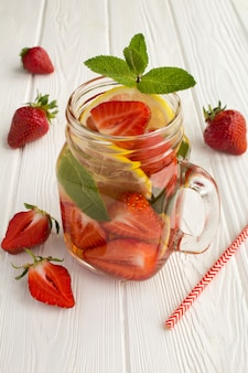 Entgiftung oder aufgegossenes wasser mit erdbeere und zitrone im glas auf der weißen holzoberfläche.