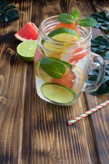 Entgiftung oder aufgegossenes wasser mit grapefruit und limette auf dem tropischen hintergrund
