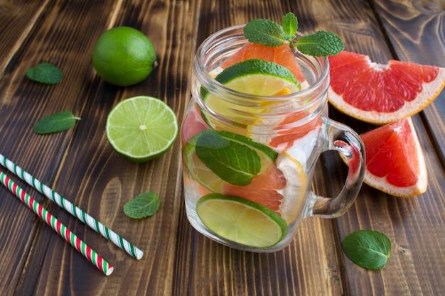 Entgiftung oder aufgegossenes wasser mit grapefruit und limette auf der braunen holzoberfläche