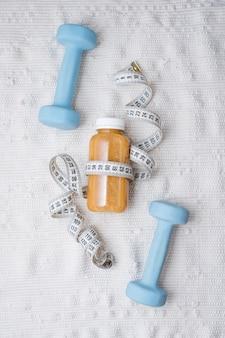 Entgiftungsgetränk mit hanteln und maßband. konzept: entgiftung und fitness, ernährung und bewegung