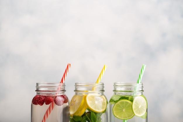 Entgiftungswasser in drei gläsern mit himbeeren, zitrone, limette und minze.