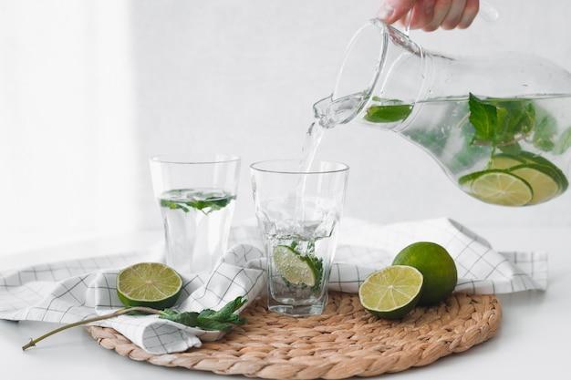 Entgiftungswasser mit limettenfrüchten. hand gießen limettenfruchtwasser aus dem krug in gläser.
