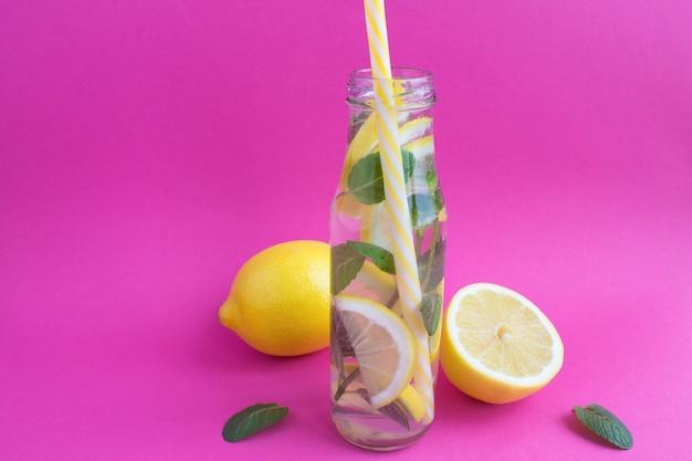 Entgiftungswasser mit zitrone und minze in der glasflasche auf dem rosa