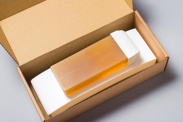Enthaarungswachskatrone und papierblätter im karton