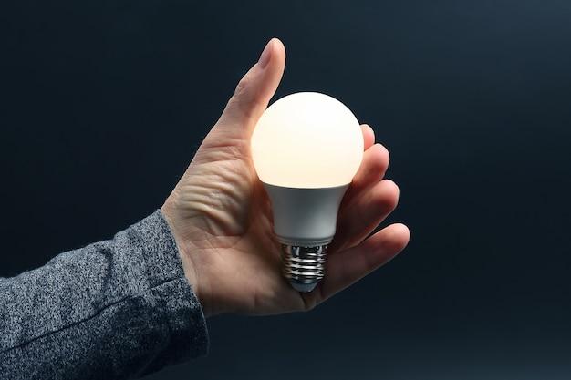 Enthaltenes led-licht in der handfläche einer person in einer dunkelheit