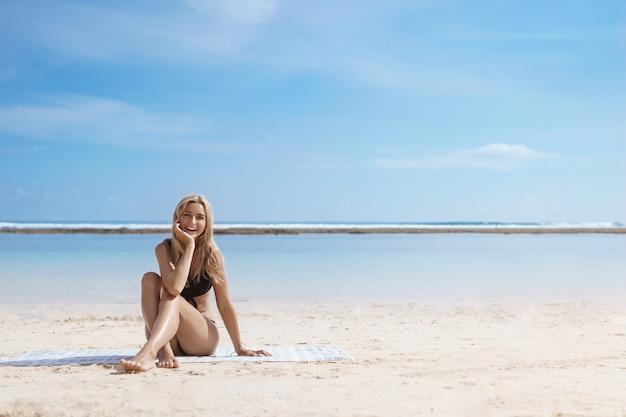 Enthusiastische blonde frau, die bikini trägt, sitzt allein am strand.