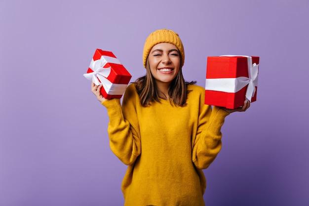 Enthusiastische dame in gestrickter mütze, die mit weihnachtsgeschenken aufwirft. fröhliches geburtstagskind, das geschenke genießt.