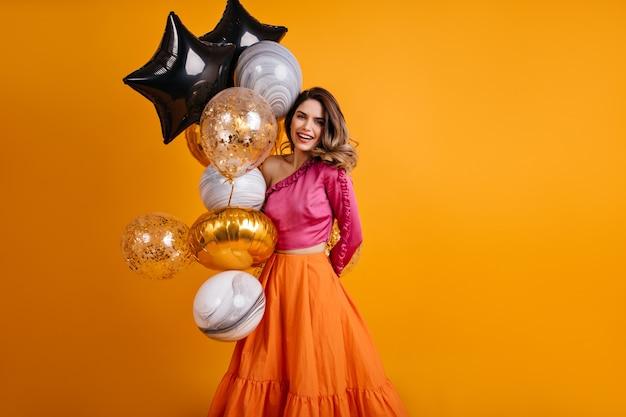Enthusiastische frau, die mit luftballons in ihrem geburtstag aufwirft