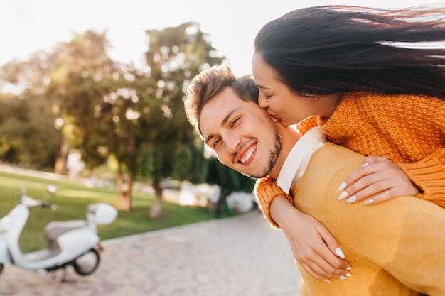Enthusiastische frau mit weißer maniküre, die lachenden mann in orange kleidung küsst