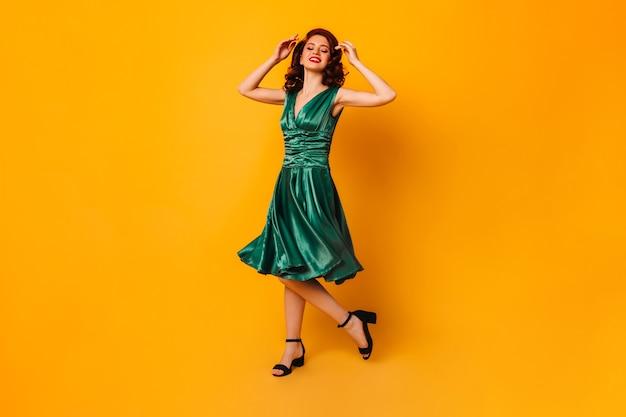 Enthusiastische ingwerfrau, die auf gelbem raum tanzt. ansicht der atemberaubenden jungen dame im grünen kleid in voller länge.