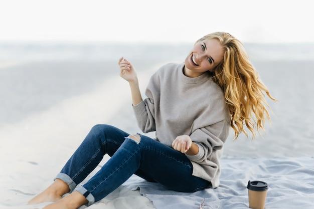 Enthusiastische kaukasische frau, die glück am herbsttag am strand ausdrückt. inspirierte junge frau in jeans, die in der natur lächeln