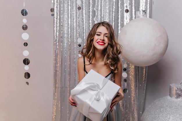 Enthusiastische weiße junge frau mit rotem lippenstift, der mit geschenk im raum aufstellt, der für partei verziert wird. interessiertes mädchen mit dem lockigen langen haar, das niedliche geschenkbox hält und lächelt.