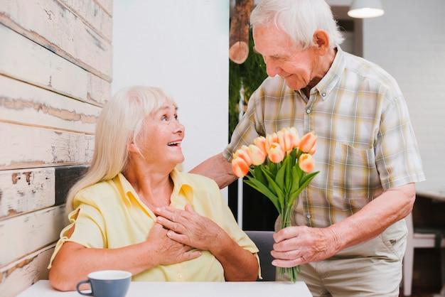 Enthusiastischer älterer mann, der blumen frau im café darstellt