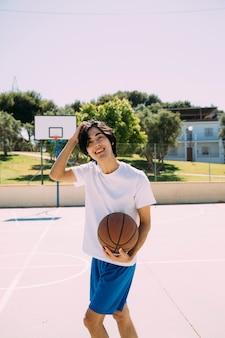 Enthusiastischer asiatischer jugendlich student, der basketball spielt