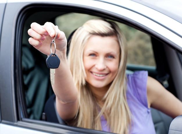 Enthusiastischer junger fahrer, der einen schlüssel hält, nachdem er ein neues auto bying gemacht hat