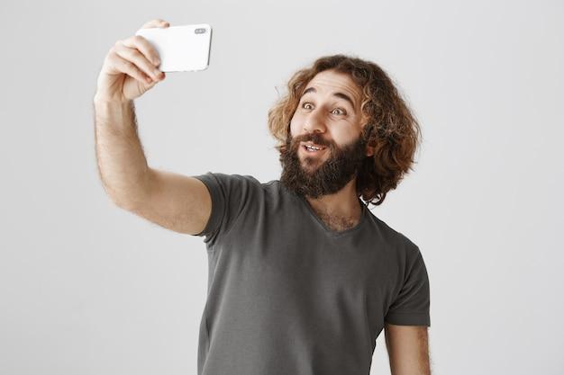 Enthusiastischer lächelnder nahöstlicher mann, der selfie mit smartphone nimmt