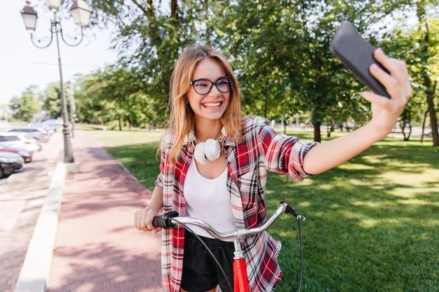 Enthusiastisches lustiges mädchen, das selfie im park macht. wunderbares blondes weibliches modell, das auf fahrrad fährt und sich selbst fotografiert.