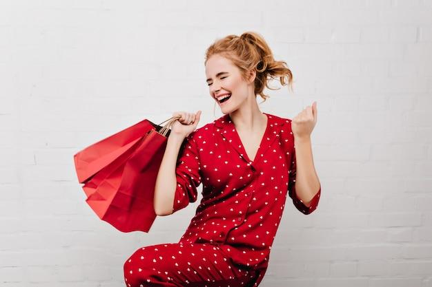 Enthusiastisches mädchen im roten pyjama tanzt mit papiertüten lokalisiert auf weißer wand lustige blonde frau, die neujahrsgeschenke hält und nahe ziegelmauer steht.