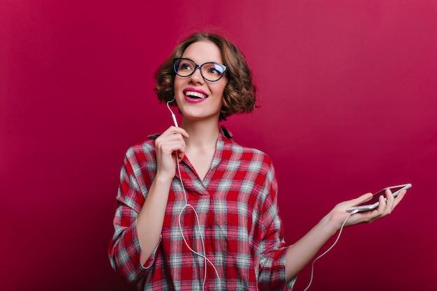 Enthusiastisches mädchen in den kopfhörern, die mit vergnügen auf rotweinwand aufwerfen. innenfoto der inspirierten lockigen jungen frau trägt eine brille und hört musik.