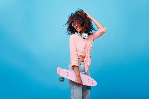 Enthusiastisches mädchen mit brauner lockiger frisur, die genießt. schlankes afrikanisches mädchen mit skateboard, das mit ihren haaren spielt und lacht.