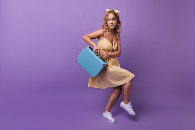 Enthusiastisches mädchen mit gewellter frisur, die vor der reise herumalbert. porträt der sorglosen blonden frau, die mit blauem koffer tanzt.