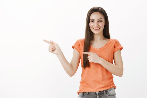 Enthusiastisches schönes brünettes mädchen, das finger nach links zeigt, fantastische promo zeigt, einladenden blick wirft, banner demonstriert