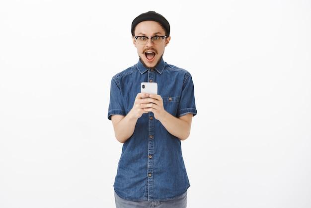 Enthusiastisches und aufgeregtes hübsches kreatives männliches modell mit schnurrbart in der brille schwarze mütze, die kiefer vor erstaunen und freude fallen lässt, smartphone hält und fantastisches unglaubliches angebot erhält