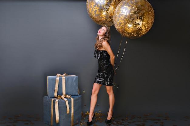 Enthusiastisches weißes mädchen mit funkelnden heliumballons, die geburtstagsfotoshooting genießen. entzückendes weibliches modell im schwarzen kleid, das mit großen geschenkboxen aufwirft und lächelt.